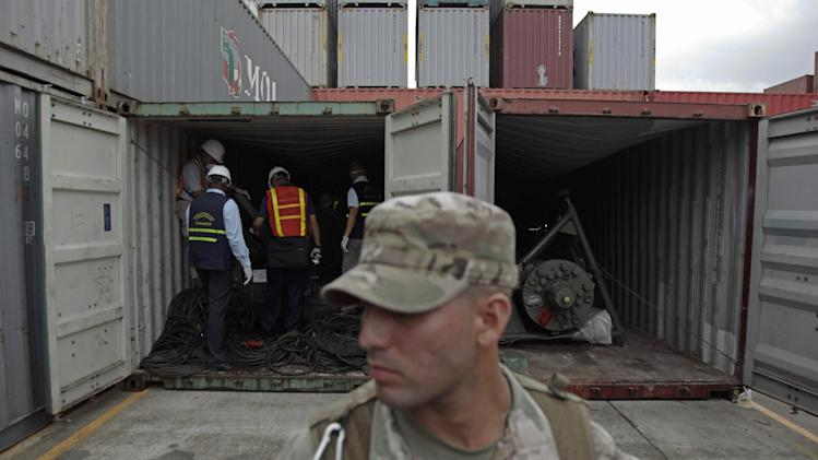 FILE - In this July 17, 2013 file photo, a police officer stands guard as investigation officers look inside a recently opened container holding military equipment aboard a North Korean-flagged freighter, at the Manzanillo International container terminal on the coast of Colon City, Panama. A Panamanian official says the two Cuban MiG-21 jet fighters found aboard the seized North Korean cargo ship were in perfect conditions to operate and that the 15 plane engines are new and could be used as replacements. (AP Photo/Arnulfo Franco, File) (AP Photo/Arnulfo Franco, File)