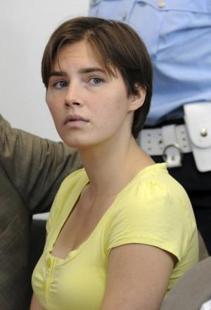 "FILE - In this Tuesday, June 1, 2010 file photo,  jailed US student Amanda Knox, center, sits between her two lawyers, during a preliminary hearing in Perugia, Italy,  Amanda Knox, the American student convicted in Italy of murdering her British roommate, is quoted as saying in a new book that she'd rather not be famous for the slaying and that her days in jail feel like ""limbo"" suspended between her old life and her hopes for the future. The 23-year-old Knox was convicted in December of murder and sexual assault in the 2007 death of her housemate, British student Meredith Kercher. She was sentenced to 26 years in prison by a court in Perugia, central Italy. (AP Photo/Fabrizio Troccoli, file)"