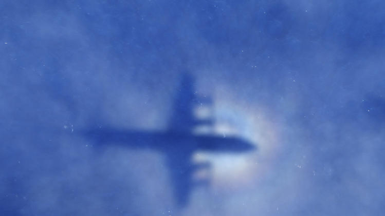 FILE - In this March 31, 2014 file photo, a shadow of a Royal New Zealand Air Force P-3 Orion aircraft is seen on low cloud cover while it searches for missing Malaysia Airlines Flight MH370 in the southern Indian Ocean. From the disappearances of aviator Amelia Earhart to labor union leader Jimmy Hoffa, there's just something about a good mystery that Americans find too tantalizing to resist. Perhaps that's why the saga of missing Malaysia Airlines Flight 370 has continued to rivet the country long after people elsewhere have moved on. (AP Photo/Rob Griffith, File)