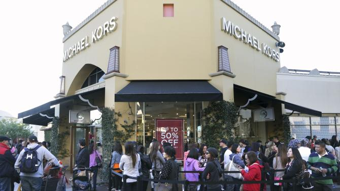 People wait in line to enter a Michael Kors store during day after Christmas sales at Citadel Outlets in Los Angeles, California