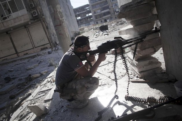 A Free Syrian Army fighter fires at Syrian Army positions during clashes in Aleppo, Syria, Tuesday, Sept. 25, 2012. Over the past few months, rebels have increasingly targeted security sites and symbols of regime power in a bid to turn the tide in Syria's 18-month conflict, which activists say has left some 30,000 people dead. (AP Photo/Manu Brabo)