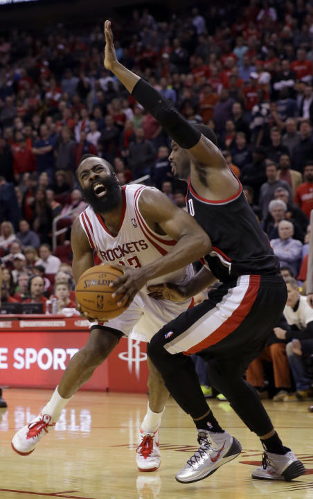 Houston Rockets shooting guard James Harden (13) is fouled by Portland Trail Blazers' Wesley Matthews (2) during the fourth quarter of an NBA basketball game Sunday, March 9, 2014, in Houston. The