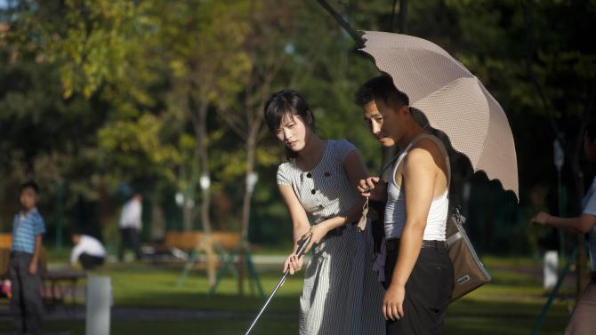 In this Sept. 8, 2012 photo, a man holds a woman's bag and parasol as they play miniature golf at a newly-built amusement park in Pyongyang, North Korea. (AP Photo/David Guttenfelder)