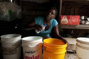 Woman puts chlorine inside buckets of water to purify it in Nigua