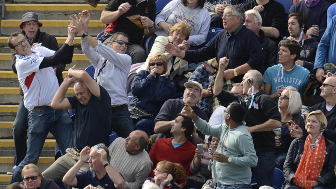 Spectators react as a ball lands in the stand hit for 6 runs by Australia's Bailey during the fourth one-day international against England at Sophia gardens in Cardiff, Wales