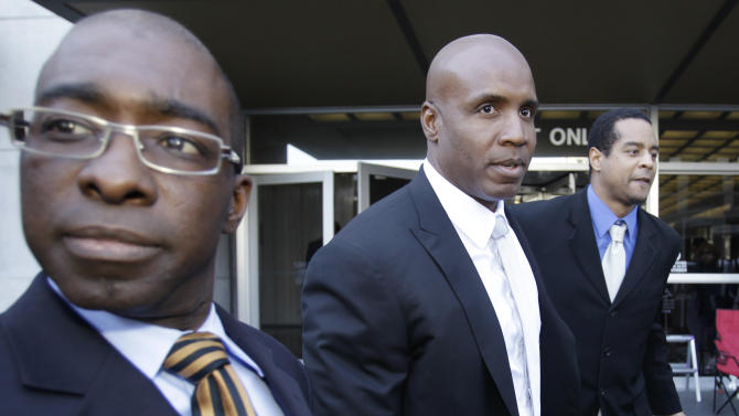 Former baseball player Barry Bonds, center, is surrounded by unidentified supporters as he leaves a federal courthouse for his perjury trial, Wednesday, April 6, 2011, in San Francisco. (AP Photo/ Paul Sakuma)