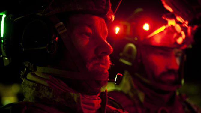"""This undated publicity film image provided by Columbia Pictures Industries, Inc. shows Joel Edgerton (left), and his brother Nash Edgerton, playing two of the SEAL Team Six soldiers as they fly a stealth blackhawk helicopter to raid Osama Bin Laden's compound in Columbia Pictures' gripping new thriller directed by Kathryn Bigelow, """"Zero Dark Thirty."""" (AP Photo/Columbia Pictures Industries, Inc., Jonathan Olley)"""