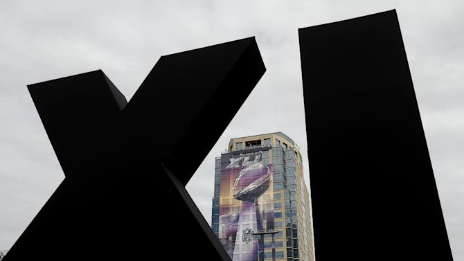 Framed by Roman numerals erected for Super Bowl XLIX, workers attach a ...