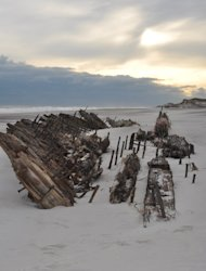The presumed remains of the Bessie White, a wrecked schooner long buried under Fire Island&#39;s dunes, now lays fully exposed on the beach following Hurricane Sandy.
