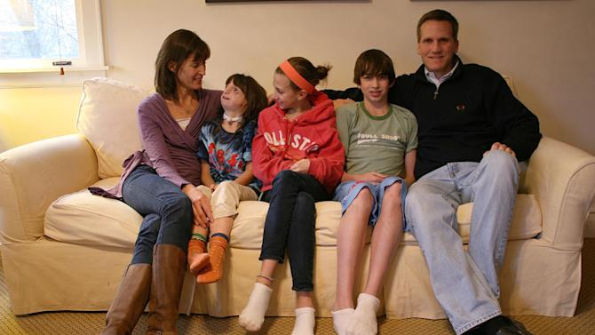 """In this Feb. 22, 2012 photo, Clara Beatty, second from left, looks at her mother, Janet Beatty, as the family poses for a family photo in their Winnetka, Ill., home. From center to left are Clara's older siblings, Gretchen and Henry, and her father Eric Beatty. Her parents discovered Clara was quite able to cope, sometimes better than they. Even today, her mother, Janet Beatty, is astounded at how well her youngest daughter navigates the world. """"Even when she was little, you could look at her and people would say there's an old soul in there,"""" she says. """"She just had these big eyes and you could see her taking everything in."""" (AP Photo/Martha Irvine)"""