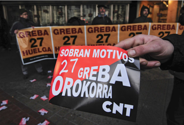 A demonstrator holds up a banner reading: ''Enough Reasons for General Strike'' during a general strike called by the Basque Nationalist trade union in Bilbao, northern Spain Thursday Jan. 27, 2011 ag