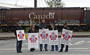 Picketers stand at the entrance to the CP Rail yards in Coquitlam