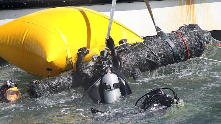 In this Thursday, June 20, 2013 photo, divers emerge with one of two cannons raised from the wreck of the Queen Anne's Revenge off the coast of Carteret County, N.C. Blackbeard captured a French slave ship and renamed it Queen Anne's Revenge in 1717. Volunteers with the Royal Navy killed Blackbeard in Ocracoke Inlet the following year, five months after the ship sank. There's a $450,000 effort under way to remove all the artifacts from the ship by the end of next year. (AP Photo/The Jacksonville Daily News, Chuck Beckley)