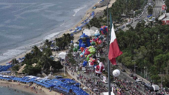 Balloons float during a Christmas parade along the waterfront of the tourist resort of Acapulco