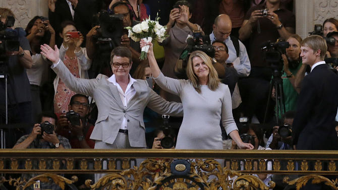 Kris Perry, left, and Sandy Stier wave after they were married at City Hall in San Francisco, Friday, June 28, 2013. Stier and Perry were married Friday, June 28, 2013, after a federal appeals court on Friday cleared the way for the state of California to immediately resume issuing marriage licenses to same-sex couples after a 4 1/2-year freeze. (AP Photo/Jeff Chiu)