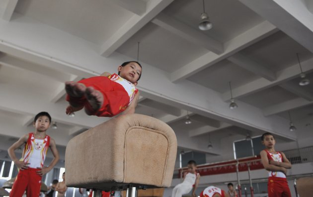 A young gymnast practices on a pommel horse during a training session at a local juvenile sports school in Jiaxing