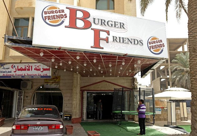 In aThursday, Aug. 23, 2012 photo, A customer stands outside Burger Friends restaurant in Baghdad, Iraq. A wave of new American-style restaurants is spreading across the Iraqi capital, enticing customers hungry for alternatives to traditional offerings like lamb kebabs and fire-roasted carp. (AP Photo/Karim Kadim)