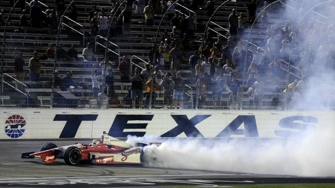 Fans look on as Justin Wilson, of England, spins out while celebrating his win in the IZOD IndyCar Firestone 550 auto race at Texas Motor Speedway, Saturday, June 9, 2012, in Fort Worth, Texas. (AP Photo/Ralph Lauer)