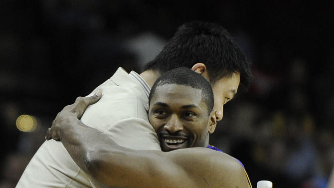 Former Houston Rockets center Yao Ming, left, greets Los Angeles Lakers' Metta World Peace, a former teammate, before an NBA basketball game Tuesday, March 20, 2012, in Houston. (AP Photo/Pat Sullivan)