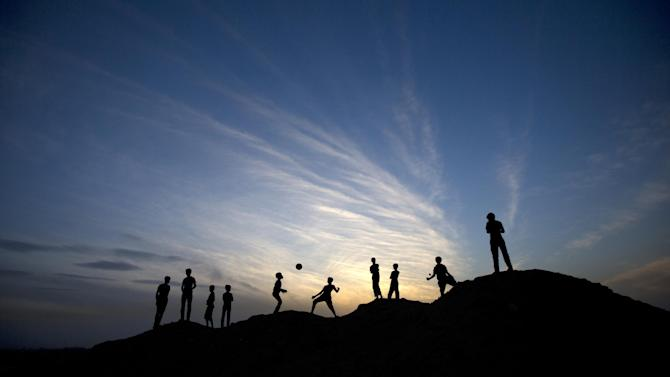 A picture taken on May 4, 2014 at sunset shows Palestinian boys playing football in Beit Lahia in the northern Gaza Strip