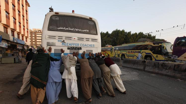 Passengers push bus to get it started along a road near a terminus in Karachi