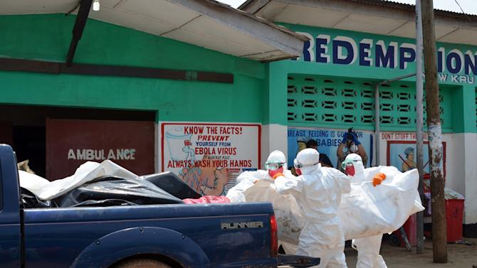 Liberian Red Cross health workers wearing protective suits carry the body of a victim of the Ebola virus, in a district of Monrovia, on September 12, 2014