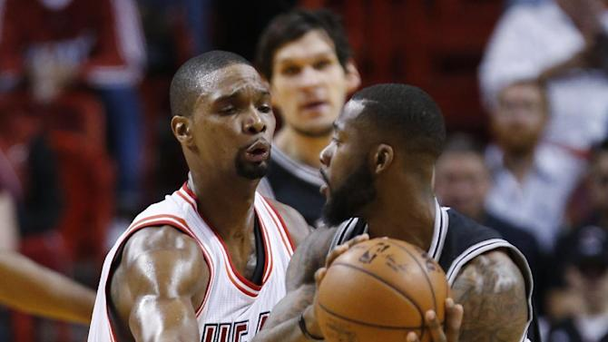 San Antonio Spurs guard Jonathon Simmons (17) looks for an opening past Miami Heat forward Chris Bosh (1) during the first half of an NBA basketball game, Tuesday, Feb. 9, 2016, in Miami. (AP Photo/Wilfredo Lee)