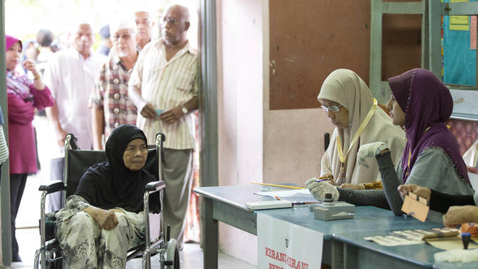 A woman waits to vote at a polling station at Penanti in Penang state in northern Malaysia, Sunday, May 5, 2013. Malaysians have begun voting in emotionally charged national elections that could see the long-ruling coalition ousted after nearly 56 years in power.   (AP Photo/Mark Baker)
