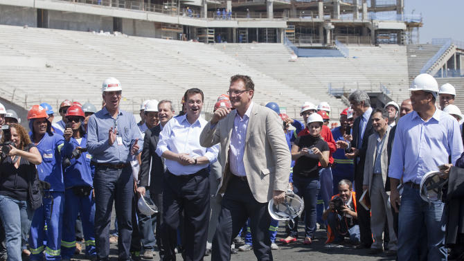 FIFA Secretary General Jerome Valcke, center, Sao Paulo's Mayor Gilberto Kassab,  center left, and Ronaldo, Brazil's former soccer player and amember of the local organizing committee for the 2014 World Cup, far right,  visit the Corinthians stadium, which is under construction and will host the opening match of the World Cup in 2014 in Sao Paulo, Brazil, Wednesday, Nov. 28, 2012. Officials are revising the construction work being done at stadiums ahead of the Confederations Cup soccer tournament in 2013 and the 2014 FIFA World Cup soccer tournament. (AP Photo/Andre Penner)
