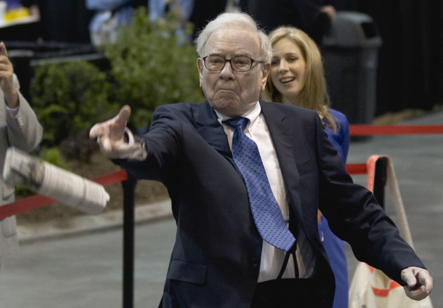 Warren Buffett, chairman and CEO of Berkshire Hathaway tosses a newspaper during a newspaper tossing competition in Omaha, Neb., Saturday, May 5, 2012. Berkshire Hathaway is holding it's annual shareholders meeting this weekend. (AP Photo/Nati Harnik)