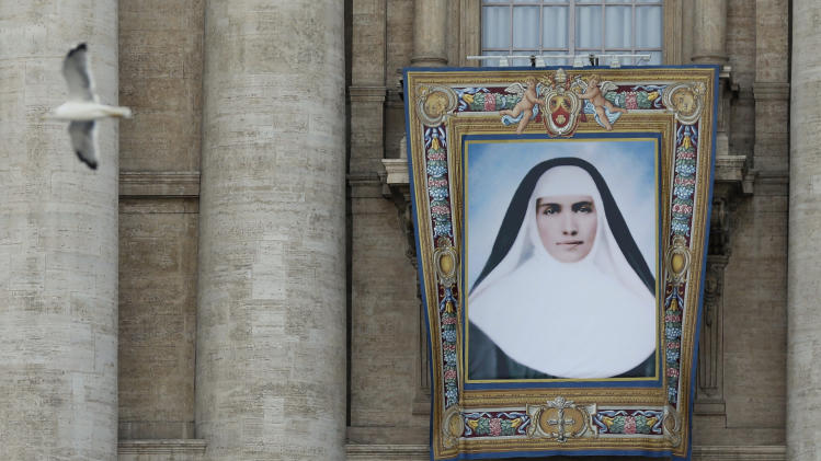 The tapestry of Mother Marianne Cope hangs from the St. Peter's Basilica, at the Vatican, Friday, Oct. 19, 2012. Mother Marianne will be one of the two US women to be declared saints along with five others in a ceremony presided over by Pope Benedict XVI at the Vatican on Sunday. (AP Photo/Alessandra Tarantino)