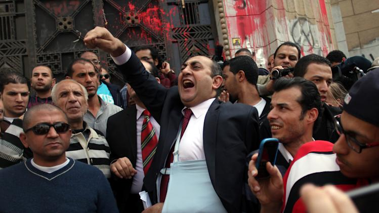 Former presidential candidate Khaled Ali, center, chants angry slogans during a protest in front of the general prosecutor's office in Cairo, Egypt, Tuesday, March 26, 2013, a day after the prosecutor general ordered the arrest of a prominent blogger and four others for allegedly instigating violence with comments posted on social media. The charges stem from clashes between supporters and opponents of the country's Islamist president last week that left 200 injured. (AP Photo/Khalil Hamra)