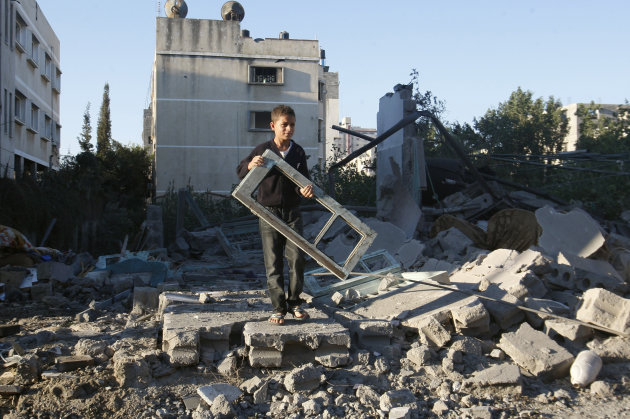A Palestinian boy holds a window pane taken from a damaged house hit in an Israeli strike, in Gaza City, Thursday, Nov. 15, 2012. Israeli aircraft, tanks and naval gunboats pounded the Hamas-ruled Gaz