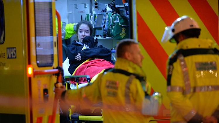 An injured woman cries inside an ambulance following a ceiling collapse at a theatre in Central London on December 19, 2013