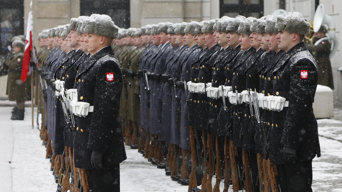 Snow falls on the troops of Poland's Guard of Honor waiting to welcome Mongolian President Tsakhia Elbegdorj in front of the Presidential Palace in Warsaw, Poland on Monday, Jan. 21, 2013. (AP Photo/Czarek Sokolowski)