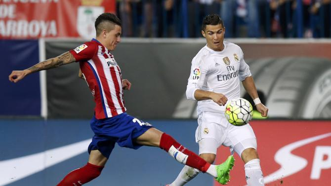 Atletico Madrid's Jose Maria Gimenez is challenged by  Real Madrid's Cristiano Ronaldo  during their Spanish first division derby soccer match in Madrid