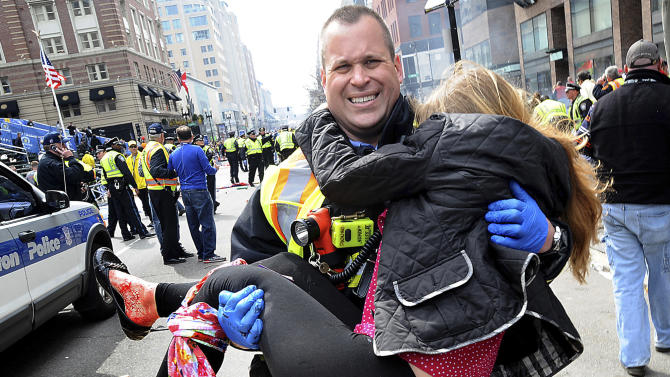 In this Monday, April 15, 2013 photo, Boston Firefighter James Plourde carries an injured girl away from the scene after a bombing near the finish line of the Boston Marathon in Boston. The FBI's investigation into the bombings at the Boston Marathon was in full swing Tuesday, with authorities serving a warrant on a suburban Boston home and appealing for any private video, audio and still images of the blasts that killed at least three and wounded more than 170. (AP Photo/MetroWest Daily News, Ken McGagh) MANDATORY CREDIT