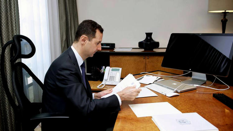 This photo released on the official Facebook page of Syrian President Bashar Assad, shows Syrian president Bashar Assad working in his office, in Damascus, Syria, Thursday, June 13, 2013. State TV quoted Transpiration Minister as saying that a mortar round fell on the edge of the airport delaying two flights that were going to land one from Latakia and one from Kuwait. The attack also delayed the take off of a Syrian flight to Baghdad. None of the planes or there passengers were hit. (AP Photo)