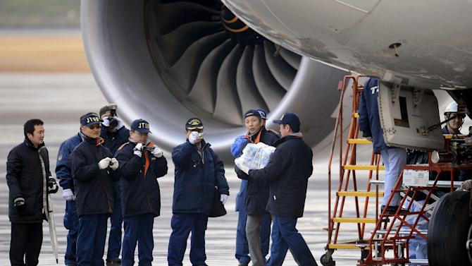An official carries a main battery that was removed from an electrical room beneath the cockpit of an All Nippon Airways Boeing 787 at Takamatsu airport in Takamatsu, western Japan, Thursday, Jan. 17, 2013. A safety official said Thursday that the battery was swollen from overheating, forcing the pilots to make the emergency landing at the airport on Wednesday. India and Europe joined the U.S. and Japan Thursday in grounding the technologically advanced aircraft because of fire risk. (AP Photo/Kyodo News)
