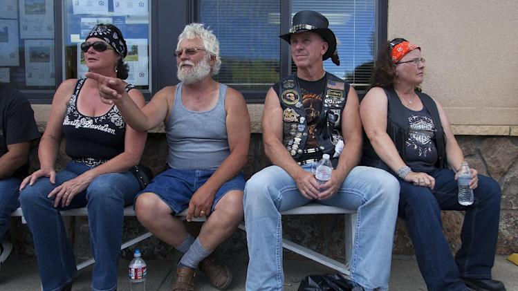Chris Root, left, her husband Bruce, Randy Warm, and his wife Kristy, enjoy some people watching during the 74th Annual Sturgis Motorcycle Rally in Sturgis, S.D, on Friday afternoon, August 1, 2014. Organizers expect attendance at this week's Sturgis Motorcycle Rally to top the estimated 466,000 who made the annual trek last year. (AP Photo/Toby Brusseau)