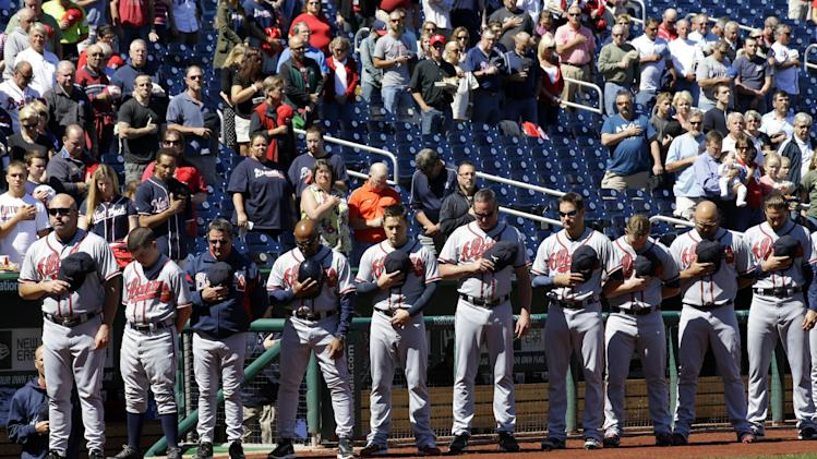 The Atlanta Braves observe a moment of silence before a baseball game against the Washington Nationals at Nationals Park Tuesday, Sept. 17, 2013, in Washington, to honor those killed and injured in Monday's attack at the nearby Washington Navy Yard. (AP Photo/Alex Brandon)