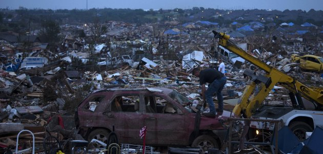 A man tows a damaged car from a property in Moore, Oklahoma, four days after the Oklahoma City suburb was left devastated by a tornado