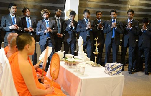 Members of the Sri Lanka cricket team watch as Sri Lankan Buddhist monks chant prayers for their success during a Buddhist ceremony in Colombo on December 6, 2013, prior to the team's departure for a