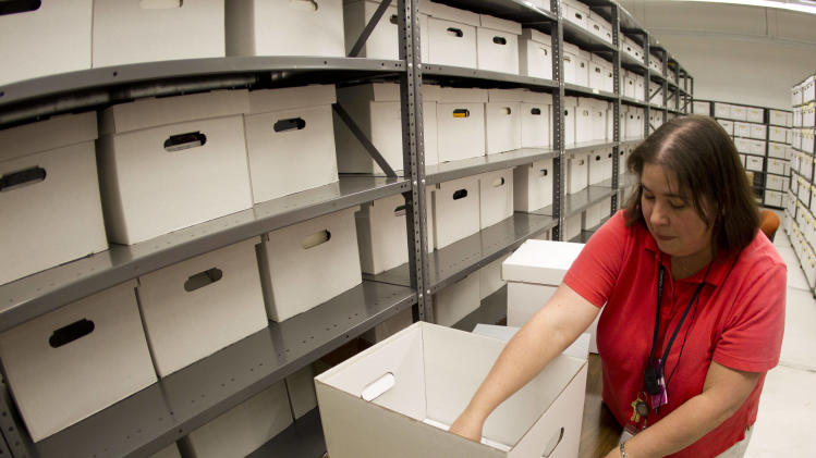 In this Wednesday, Oct. 17, 2012 photo, Archivist Amanda Mros files microfilm at the Georgia State Archives in Morrow, Ga. The Georgia State Archives will remain open to the public two days a week after an uproar over plans to limit access to appointments only for six days a month, state officials said Thursday, Oct. 18, 2012. Gov. Nathan Deal and Secretary of State Brian Kemp said $125,000 of a planned $733,000 cut in funding would be restored. (AP Photo/John Bazemore)