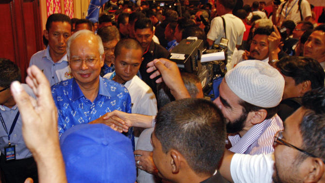 Malaysian Prime Minister Najib Razak, left, is congratulated by supporters after winning the national elections in Kuala Lumpur, Malaysia, early Monday, May 6, 2013. Malaysia's long-governing coalition won national elections Sunday to extend its 56 years of unbroken rule, fending off the strongest opposition it has ever faced but exposing vulnerabilities in the process. (AP Photo/Lai Seng Sin)