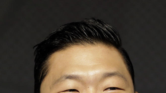"""FILE - In this Sept. 25, 2012 file photo, South Korean rapper PSY, who sings the popular """"Gangnam Style"""" song, smiles during a press conference in Seoul, South Korea. As """"Gangnam Style"""" gallops toward 1 billion views on YouTube, the first Asian pop artist to capture a massive global audience has gotten richer click by click. So too has his agent and his grandmother. But the money from music sales isn't flowing in from the rapper's homeland South Korea or elsewhere in Asia. With one song, 34-year-old Park Jae-sang — better known as PSY — is set to become a millionaire from YouTube ads and iTunes downloads, underlining a shift in how money is being made in the music business. (AP Photo/Lee Jin-man, File)"""