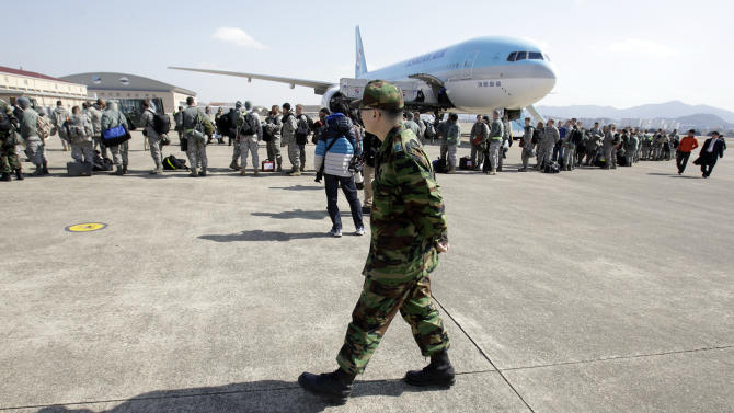 A South Korean soldier looks at U.S. soldiers who just arrived from Kadena air base on Okinawa of Japan, by a civil aircraft to take part in joint military drills between U.S. and South Korea, at Daegu military air base in Daegu, south of Seoul, South Korea, Tuesday, March 8, 2011. South Korean and U.S. troops kicked off their annual drills last week, while North Korea slammed the maneuvers as a rehearsal for invasion that could trigger a nuclear war on the divided peninsula.  (AP Photo/ Lee Jin-man)