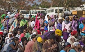 Displaced women, including foreigners, queue inside …