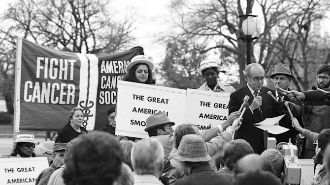 "FILE - In this Nov. 15, 1979 file photo, United States Surgeon General Dr. Julius B. Richmond, at the microphones, kicks off the third annual ""Smokeout"" rally sponsored by the American Cancer Society in Washington, D.C. as a part of the ""Great American Smokeout Day."" (AP Photo)"