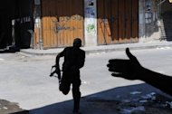 A rebel runs across the street at a checkpoint in the city in Aleppo on August 18. UN observers wound up their troubled mission to Syria at midnight on Sunday in the face of the escalating violence and a failure by world powers to agree on how to tackle Assad and bring about peace to the strategically vital Middle East state